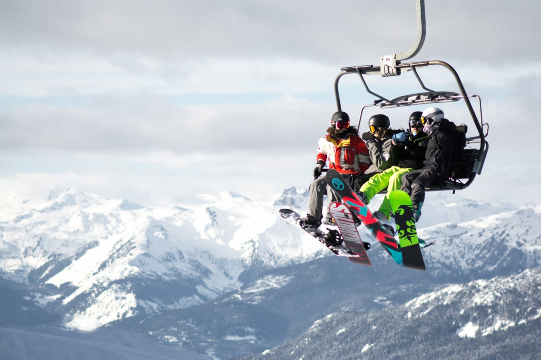Auslands-Reisekrankenversicherung Winter Snowboarder Lift Berge Auslandsreisekrankenversicherung