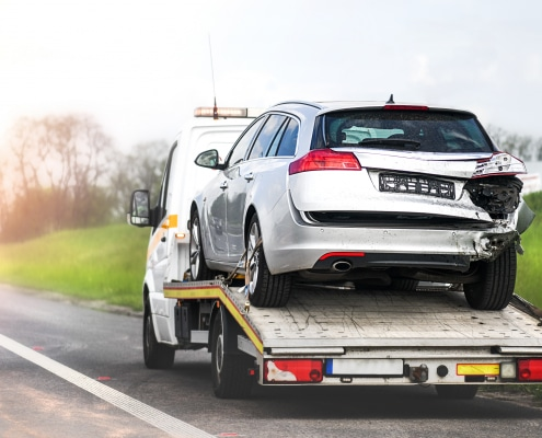 Loading broken car on a tow truck. Damage vehicle after crash accident on the highway road. Schutzbrief Christian Willmann Versicherungsmakler Mannheim